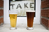Two glasses of beer in front of Take Away sign