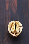 Half a walnut on wooden background