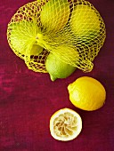 Lemons in net bag, whole lemon and squeezed lemon half