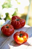 Three tomatoes (variety 'Vierländer Krause') on wooden table