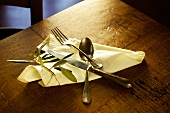 Cutlery on a serviette with an olive sprig