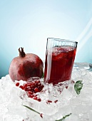 Pomegranate juice and a pomegrante on ice