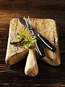 A chopping board with a carving knife and fork, parsley and peppercorns