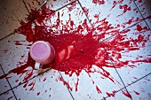 A measuring jug of strawberry puree spilt on the kitchen floor