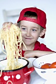A little boy taking spaghetti out of a pan