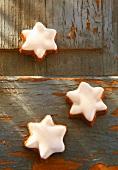 Three cinnamon stars on a wooden surface