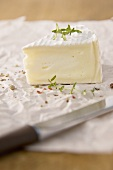 A piece of camembert with thyme and pepper