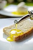 Brotscheibe mit Olivenöl beträufeln