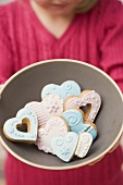 A girl holding a bowl of heart-shaped biscuits