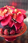 Chocolate cake with strawberries and rose petals