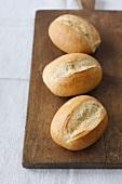 Three bread rolls on a chopping board