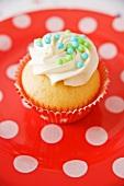 A vanilla cupcake with sugar balls