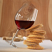 A glass of red wine and a stack of biscuits