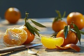 Tangerines with leaves, partially peeled