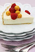 A slice of vanilla tart with cape gooseberries and raspberries