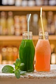 A cucumber smoothie and a melon smoothie in bottles with straws