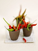 Several small, hot chili peppers in three small bowls