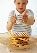 Boy sprinkling icing sugar over a pile of waffles