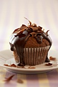 A chocolate muffin with chocolate sauce & chocolate curls