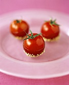 Three cherry tomatoes with sesame seeds sticking to them