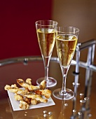 Cheese sticks with anchovies and two glasses of champagne