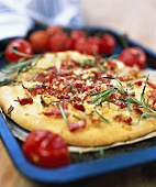 Pizza with cherry tomatoes, rosemary and diced bacon