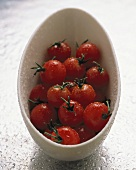 Several cherry tomatoes in a white dish