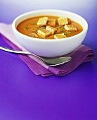 Creamed tomato soup with croutons on a napkin