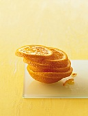 Slices of orange in a pile on a sheet of glass
