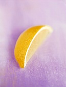 Wedge of lemon on violet background