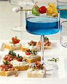 Blue Curacao cocktail as aperitif with snacks