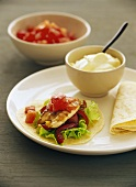 Chicken with tomatoes, green salad and peppers on tortillas