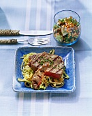Grilled rump steak on salad leaves with fruit & leek salad