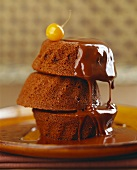 Three chocolate buns in a pile with chocolate sauce