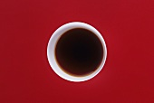 Soy sauce in a small white bowl on red background