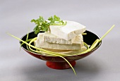Several slices of tofu in a bowl
