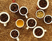 Several coffee beans, roasted and unroasted, in cups