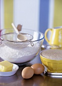 Baking still life with flour, eggs, butter & baking utensils