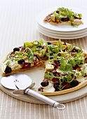 Pizza with olives, artichokes and rocket with pizza cutter