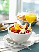 Breakfast table with a bowl of fruit and orange juice
