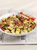 Chicken with sesame and vegetables on a newspaper