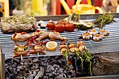 Assorted barbecued dishes on a grill rack