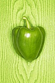 Green pepper against green wooden background