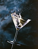 Ice-cold Martini splashing out of a glass