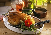 Roast duck with herb stuffing on a wooden table