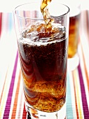 Cola wird in ein Glas eingeschenkt