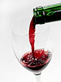 Red wine being poured into an empty glass
