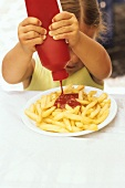 Girl squeezing ketchup over chips