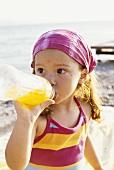 Mädchen am Strand trinkt aus einer Plastikflasche
