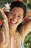 Smiling woman with exotic flowers in her hair